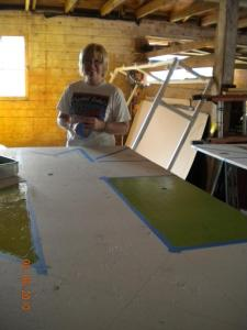 Ann Viger works on taping and painting.